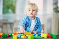 Kleiner Junge, der mit bunten Plastikbaublöcken spielt Lizenzfreies Stockfoto