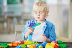 Kleiner Junge, der mit bunten Plastikbaublöcken spielt Stockfotografie