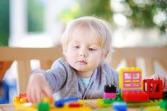 Kleiner Junge, der mit bunten Plastikblöcken am Kindergarten spielt stockbild