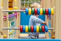 Kleiner Junge, der mit einem Abakus spielt Lizenzfreies Stockfoto
