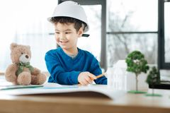 Kleiner Junge, der mit einem Bären im Architektenbüro spielt Lizenzfreies Stockfoto