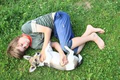 Kleiner Junge, der mit einem Hund schläft Lizenzfreie Stockfotos