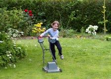 Kleiner Junge, der mit einem Rasenmäher im Garten läuft Stockbild