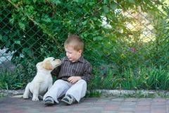 Kleiner Junge, der mit einem Welpen Labrador im Park spielt Stockfotografie