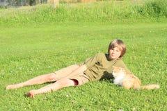 Kleiner Junge, der mit einer Katze spielt Lizenzfreies Stockfoto