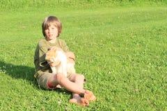 Kleiner Junge, der mit einer Katze spielt Lizenzfreie Stockfotos