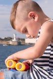Kleiner Junge, der mit Ferngläsern auf dem Hintergrund des Meeres und des Leuchtturmes spielt Stockbilder