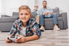 Kleiner Junge, der mit gamepad auf Boden im Wohnzimmer, Videospiele spielend liegt, während sein Vater und Großvater sind lizenzfreies stockbild