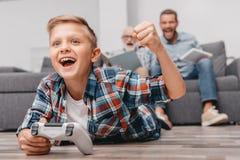 Kleiner Junge, der mit gamepad auf dem zujubelnden Boden liegt, während sein Vater und Großvater sind stockfotografie