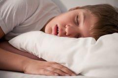 Kleiner Junge, der mit geöffnetem Mund schläft Stockbilder