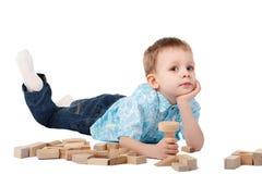 Kleiner Junge, der mit hölzernem Designer auf dem Boden spielt lizenzfreie stockfotografie