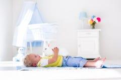 Kleiner Junge, der mit Kaninchenhaustier spielt Stockbild