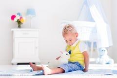 Kleiner Junge, der mit Kaninchenhaustier spielt Stockfoto