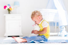 Kleiner Junge, der mit Kaninchenhaustier spielt Lizenzfreie Stockbilder