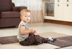 Kleiner Junge, der mit Kieseln spielt Stockbild