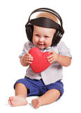 Kleiner Junge, der mit Kopfhörern, seine Hände halten Herz lokalisiert sitzt Stockfotos