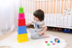 Kleiner Junge, der mit pädagogischem Spielzeug spielt Stockfotografie