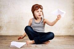 Kleiner Junge, der mit Papierflugzeugen spielt Lizenzfreie Stockfotos