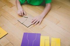 Kleiner Junge, der mit Puzzlespiel, Bildung und dem Lernen spielt Lizenzfreie Stockfotos
