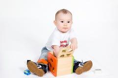 Kleiner Junge, der mit Puzzlespielwürfel spielt stockfotos