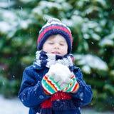 Kleiner Junge, der mit Schnee im Winter, draußen spielt Stockfotografie