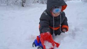 Kleiner Junge, der mit Schnee spielt stock video