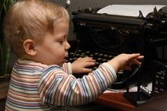 Kleiner Junge, der mit Schreibmaschine und Newtonwiege spielt Stockbild