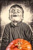 Kleiner Junge, der mit Schwierigkeit einen großen Kürbis hält Halloween sie Stockfotografie