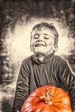 Kleiner Junge, der mit Schwierigkeit einen schweren Kürbis hält Halloween t Stockfotos