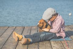 Kleiner Junge, der mit seinem Hund durch den Fluss spielt lizenzfreies stockbild
