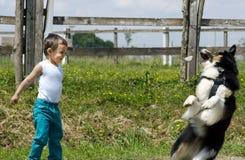 Kleiner Junge, der mit seinem Hund spielt Lizenzfreies Stockbild