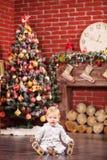 Kleiner Junge, der mit seinem Spielzeug durch Weihnachtsbaum spielt Stockbild