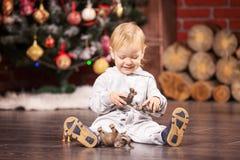 Kleiner Junge, der mit seinem Spielzeug durch Weihnachtsbaum spielt Stockfotografie