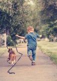 Kleiner Junge, der mit seinem Spürhundwelpen läuft Stockfotografie
