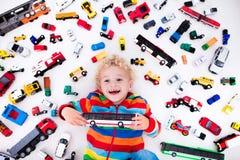 Kleiner Junge, der mit Spielzeugautos spielt Stockbild