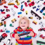 Kleiner Junge, der mit Spielzeugautos spielt Stockfotografie