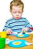 Kleiner Junge, der mit Spielzeugküche spielt lizenzfreie stockfotos