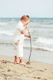 Kleiner Junge, der mit Stock auf dem Strand, im Freien spielt, Stockbild