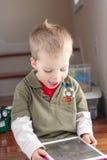 Kleiner Junge, der mit Tablette spielt Stockfoto