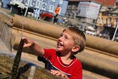 Kleiner Junge, der mit Wasser spielt Lizenzfreie Stockbilder