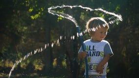 Kleiner Junge, der mit Wasser spielt stock video