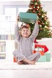 Kleiner Junge, der mit Weihnachtsgeschenk lacht Lizenzfreies Stockfoto