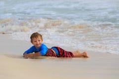 Kleiner Junge, der mit Wellen auf Sandstrand spielt Lizenzfreie Stockfotos