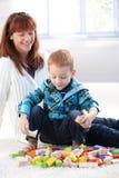 Kleiner Junge, der mit Würfelmutterdem überwachen spielt Lizenzfreies Stockbild