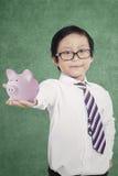 Kleiner Junge, der moneybox zeigt Stockfotografie