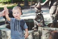 Kleiner Junge, der nahe bei Brunnen im nassen T-Shirt steht Stockfotografie