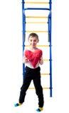 Kleiner Junge, der nahe bei bunter Treppe steht und ein rotes Herz hält Lizenzfreies Stockbild