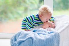 Kleiner Junge, der neugeborenen Babybruder küsst stockfotografie