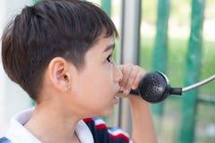 Kleiner Junge, der Notruf des allgemeinen Telefons im Freien verwendet lizenzfreie stockfotos