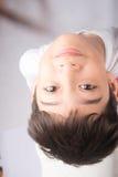 Kleiner Junge, der oben mit dem Lächeln auf weißem Hintergrund schaut Lizenzfreies Stockbild